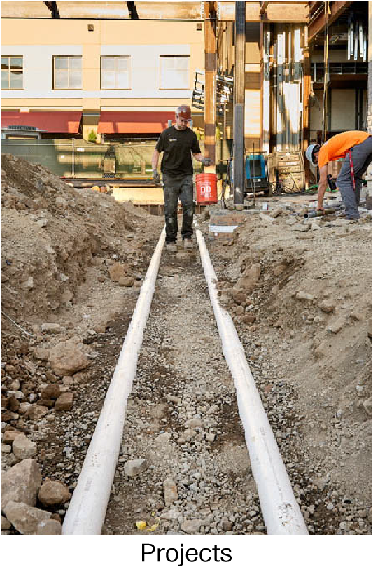 Man with bucket walking between two vertically parallel pipes in the ground.